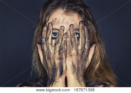 Scared young woman with dirty face and arms on dark background