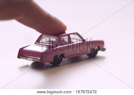front view closeup of finger pushing forward a little miniature pink toy car on light background