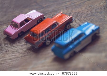 horizontal low angle view closeup of three colored vintage toy cars on brown wood floor selective focus copyspace