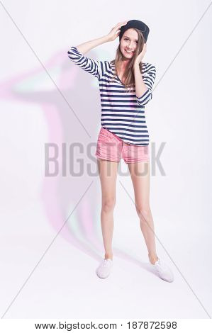 Full Length Portrait of Happy Smiling Caucasian Brunette in Hat and Striped Shirt. Posing Against White Backgroud. Hands Lifted. Vertical Image Orientation