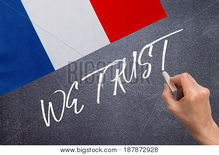 WE TRUST on the chalk board and the flag of France. Election concept