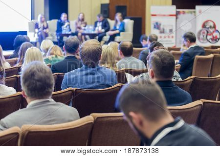 Business Meetings Ideas and Concepts. Many People at the Law Conference Listening to The Group of Hosts Sitting At The Round Table on Stage. Horizontal Image Composition