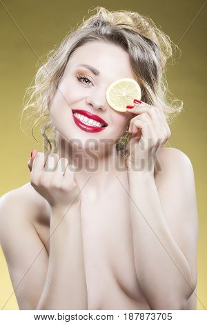 Lemon Fruit Series. Portrait of Sexy Naked Caucasian Blond Girl Making Faces with Lemon Slice Against Yellow Background.Vertical Image Composition