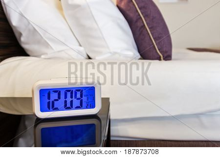 Cushions and dressed bed linen and electronic alarm clock on the bed in the hotel
