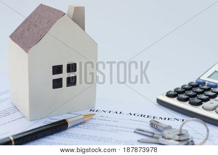 rental agreement contact with an architectural model and a calculator and pen and keys no logo or trademark