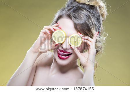 Sexy Fruit Series. Closeup Portrait of Cute Funny Naked Caucasian Girl Holding A Pair of Lemon Slices In Front of Her Eyes with Smile. Against Yellow. Horizontal Image Composition