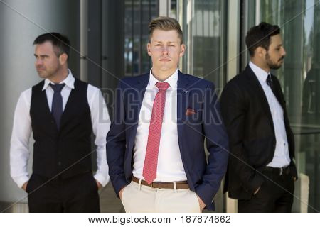 three handsome young businessmen standing outside in front of office building