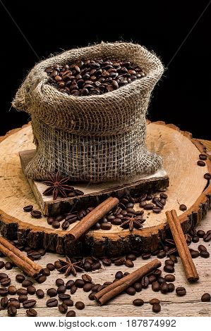 Coffee beans in a canvas bag on wooden background