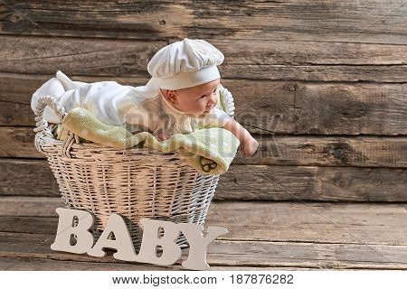 Basket and baby, wooden background. Little child lying on towel.