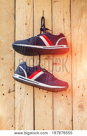pair of sport shoes hang on a nail on a brown wooden wall. Toned