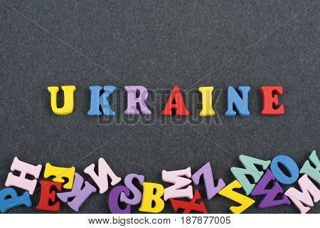 UKRAINIAN word on black board background composed from colorful abc alphabet block wooden letters, copy space for ad text. Learning english concept