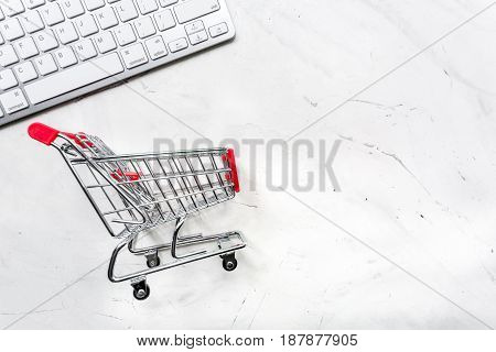 mini trolley, keyboard for online purchasing on stone desk background top view mockup