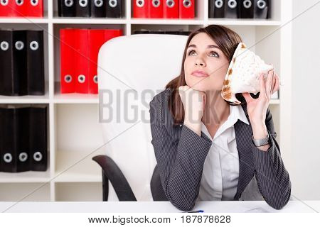 Close up portrait of cute young woman sitting in the office while working and dreaming about vacation on islands