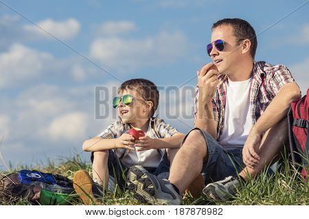 Father And Son Sitting In The Field At The Day Time.