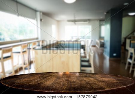 Selected focus empty brown wooden table and Coffee shop or cafe blur background with bokeh image. for your photomontage or product display