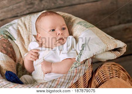 Adorable little kid. Caucasian baby boy in basket.