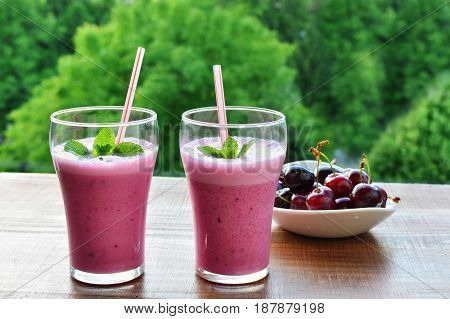 Healthy pink smoothie liquid food with Greek yogurt in glasses on wooden table outdoors