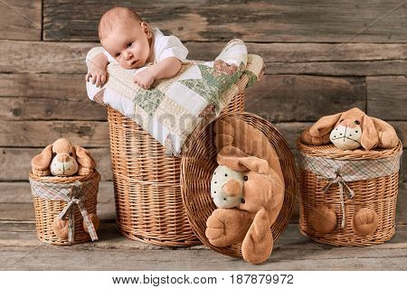 Child and baskets, wooden background. Cute caucasian kid.