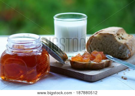 Bread with homemade apple jam on a wooden board with a jar of jam and milk