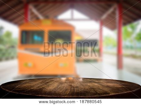 Selected focus empty brown wooden table and train station or transportation blur background image. for your photomontage or product display