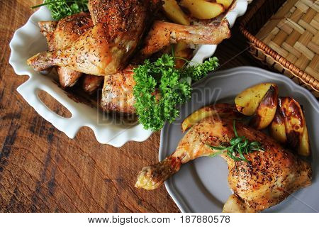 Grilled chicken legs c with potato for garnish. Top view. Wooden background.