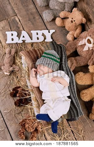 Baby and teddybears, top view. Small child lying on hay.