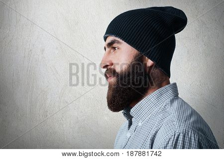 A Sideways Portrait Of Stylish Bearded Man Wearing Checked Shirt And Black Cap Having Tatoo On His N