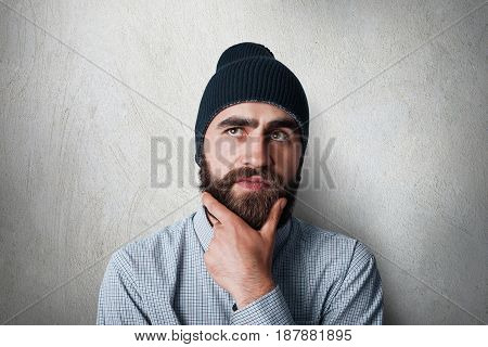 A Studio Portrait Of Stylish Man With Thick Black Beard Wearing Black Cap And Casual Checked Shirt H