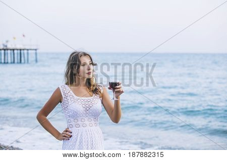 Beautiful woman on the beach with a glass of wine in white dress relaxes happy