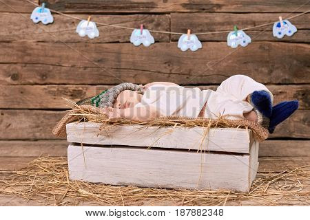 Baby sleeping on straw. Wooden box and little child. Healthy sleep habits.
