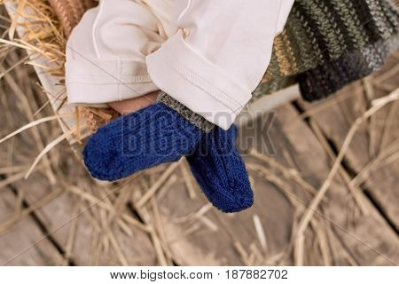 Baby legs in socks. Blue knitted wool. Dressing your baby for winter.