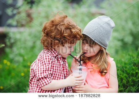 photo of two cute hipsters drinking cocktail in park