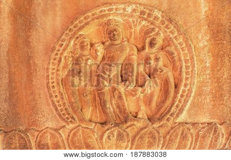 Man and two woman figures on stone wall relief of 7th century Hindu temple, town Aihole, India. Carved architecture of Asia