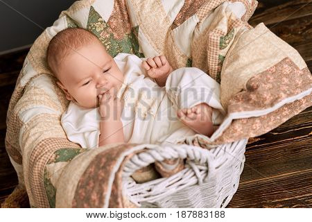 Blanket, basket and baby. Cute small child.
