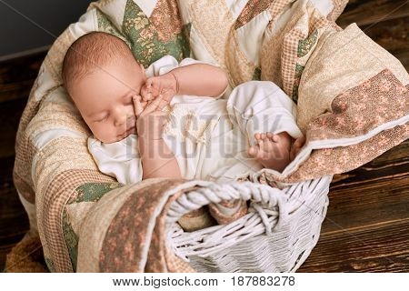 Sleepy child in a basket. Cute infant touching his face. How much sleep babies need.