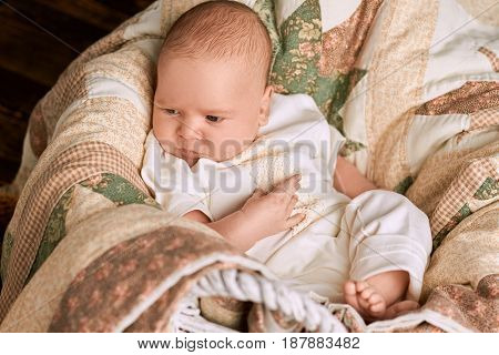 Adorable caucasian child. Little kid and blanket. Tips for choosing baby names.