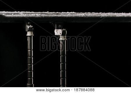 Closeup. Gymnastic parallel bars. Isolated on black background with fog