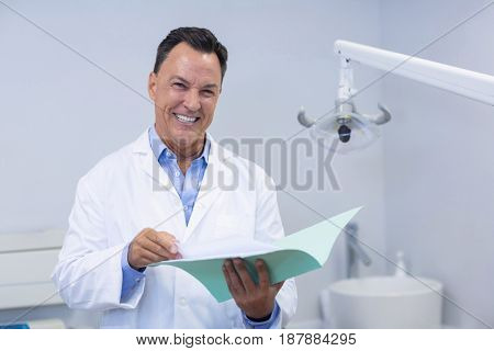 Portrait of smiling dentist holding file in dental clinic