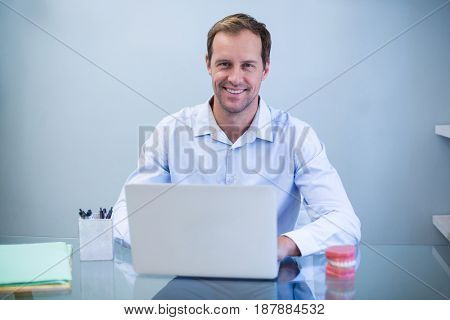 Portrait of smiling dentist working on laptop in dental clinic