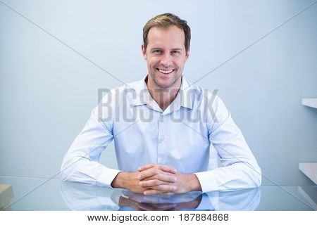 Portrait of happy dentist sitting at desk in clinic