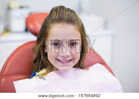 Smiling young patient sitting on dentists chair in dental clinic