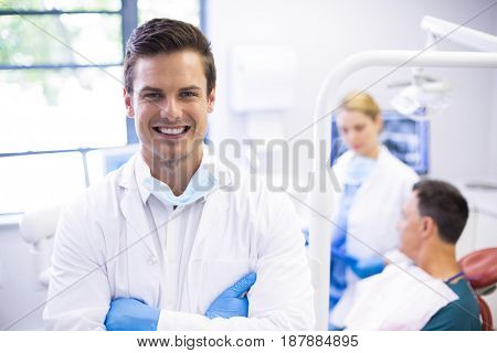 Portrait of dentist standing with arms crossed while his colleague examining patient in background