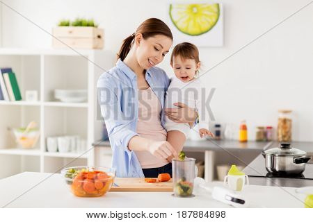 family, food, healthy eating, cooking and people concept - happy mother adding chopped vegetables to blender cup and holding little baby girl at home kitchen
