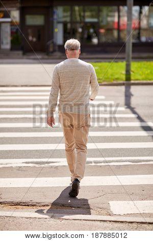 leisure and people concept - senior man walking along summer city crosswalk