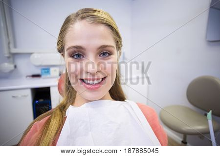 Portrait of smiling female patient sitting on dentists chair in clinic