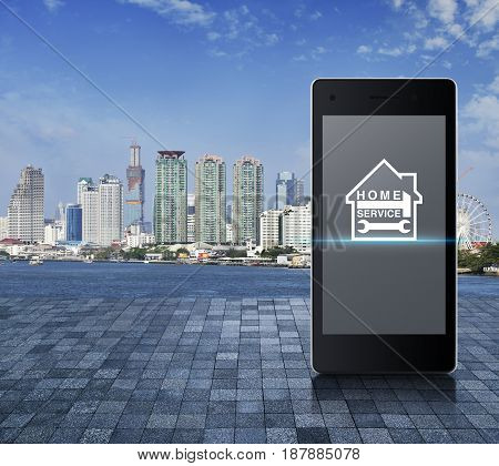 Hammer and wrench with house icon on modern smart phone screen on on stone tile floor over modern city tower river and blue sky Home service concept