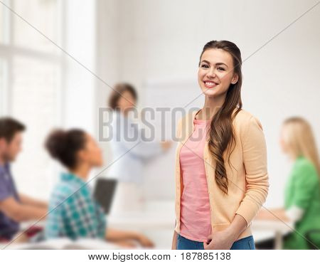 education, high school and people concept - happy smiling young student woman over classroom background