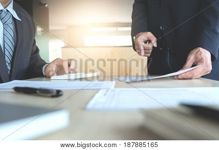 Businessman analysis on calculator new plan financial graph data with business colleagues pointing at paperwork in the office.