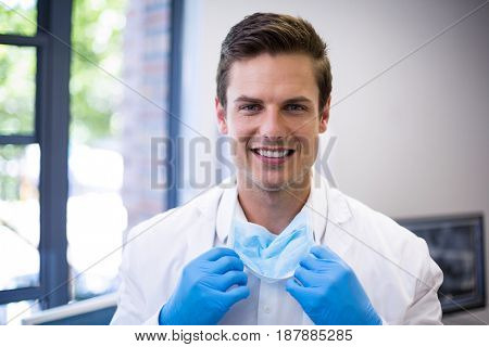 Portrait of happy dentist holding surgical mask in clinic