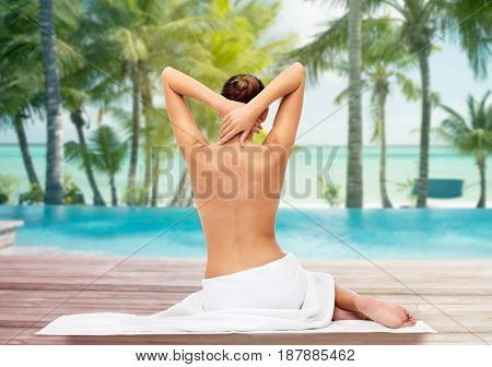 beauty, people and bodycare concept - beautiful young woman in white towel with bare top over beach and outdoor swimming pool background